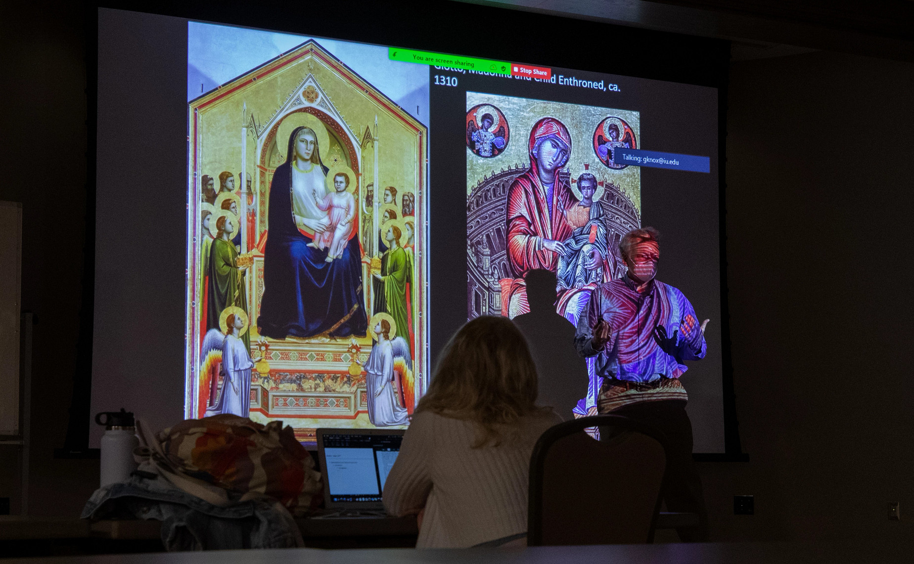 A professor shows a class slides of paintings in a darkened classroom