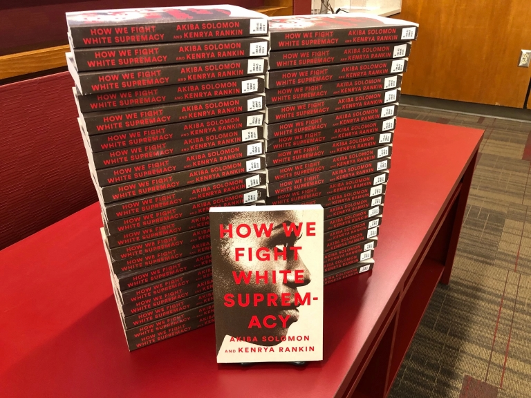 "Copies of the book ""How We Fight White Supremacy"" are stacked on a table."