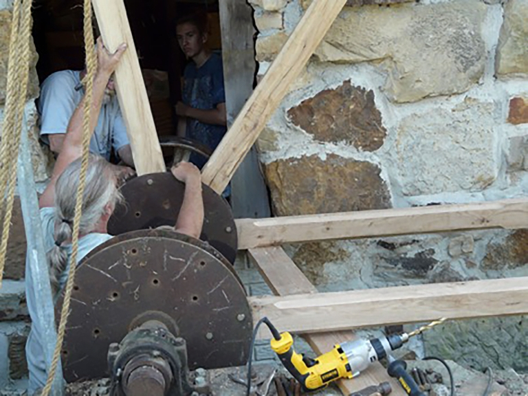Dotson and Borders work to assemble the waterwheel