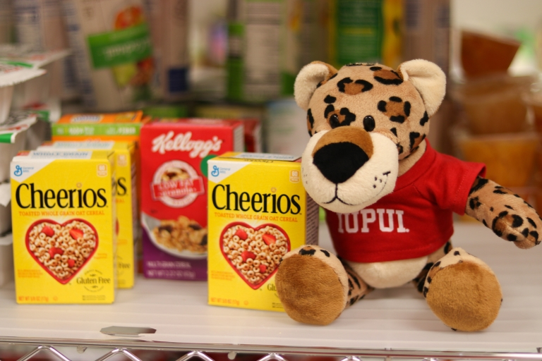 Stuffed jaguar wearing IUPUI t-shirt sits next to a box of Cheerios on a shelf in Paws' Pantry.