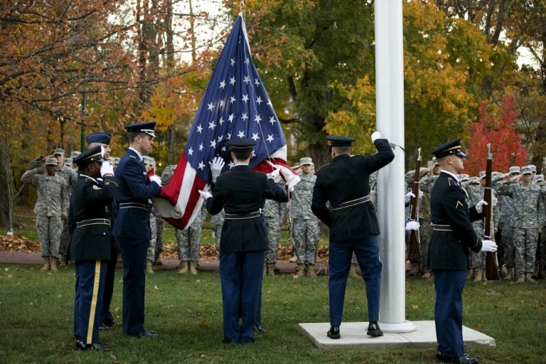 Service members display the United States flag on a pole