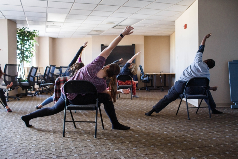 Participants sit in chairs and stretch during a chair yoga class