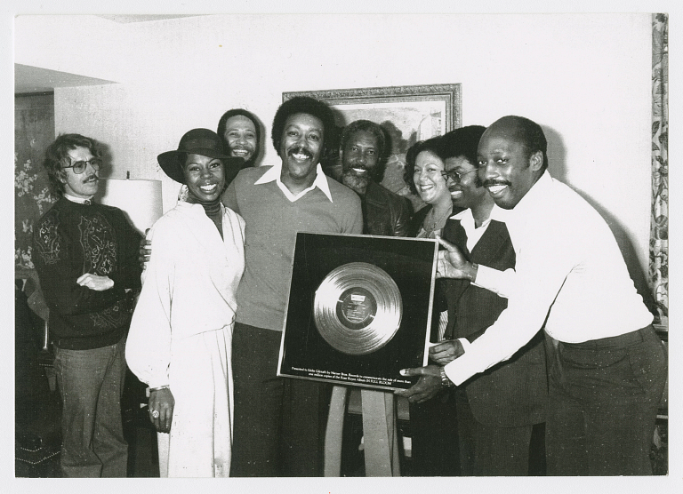 Group of people smile while holding gold record