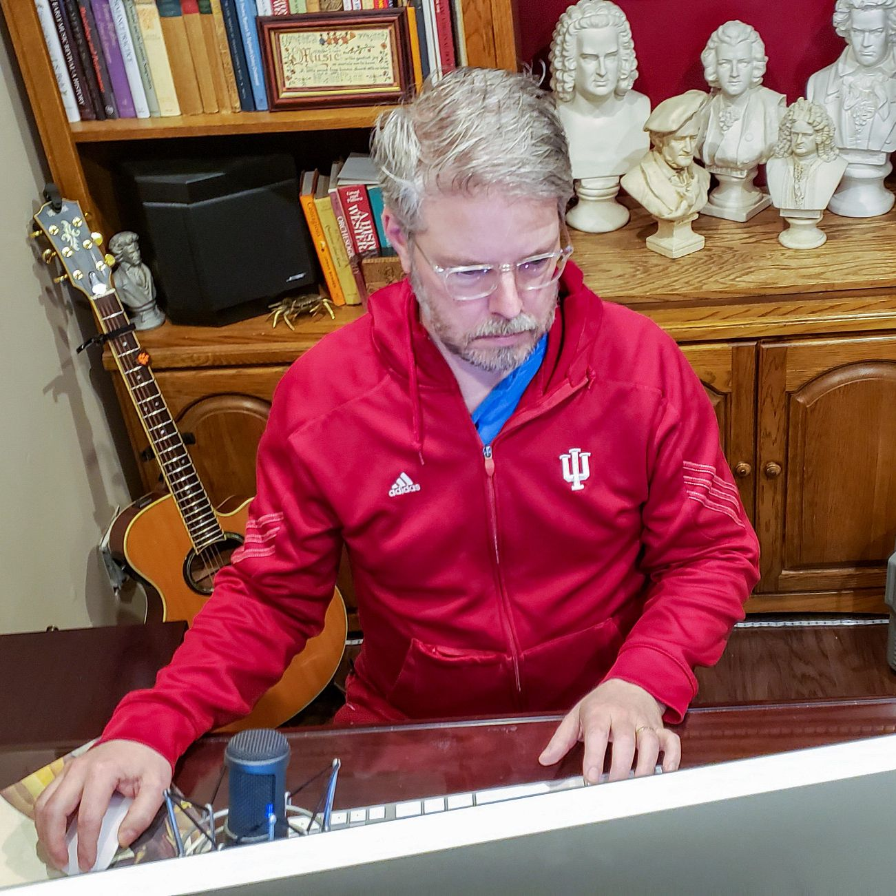 A man in a red IU jacket works at his home computer