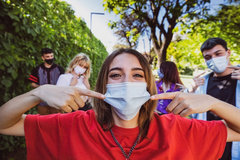 a group of people outside wearing masks and looking at the camera