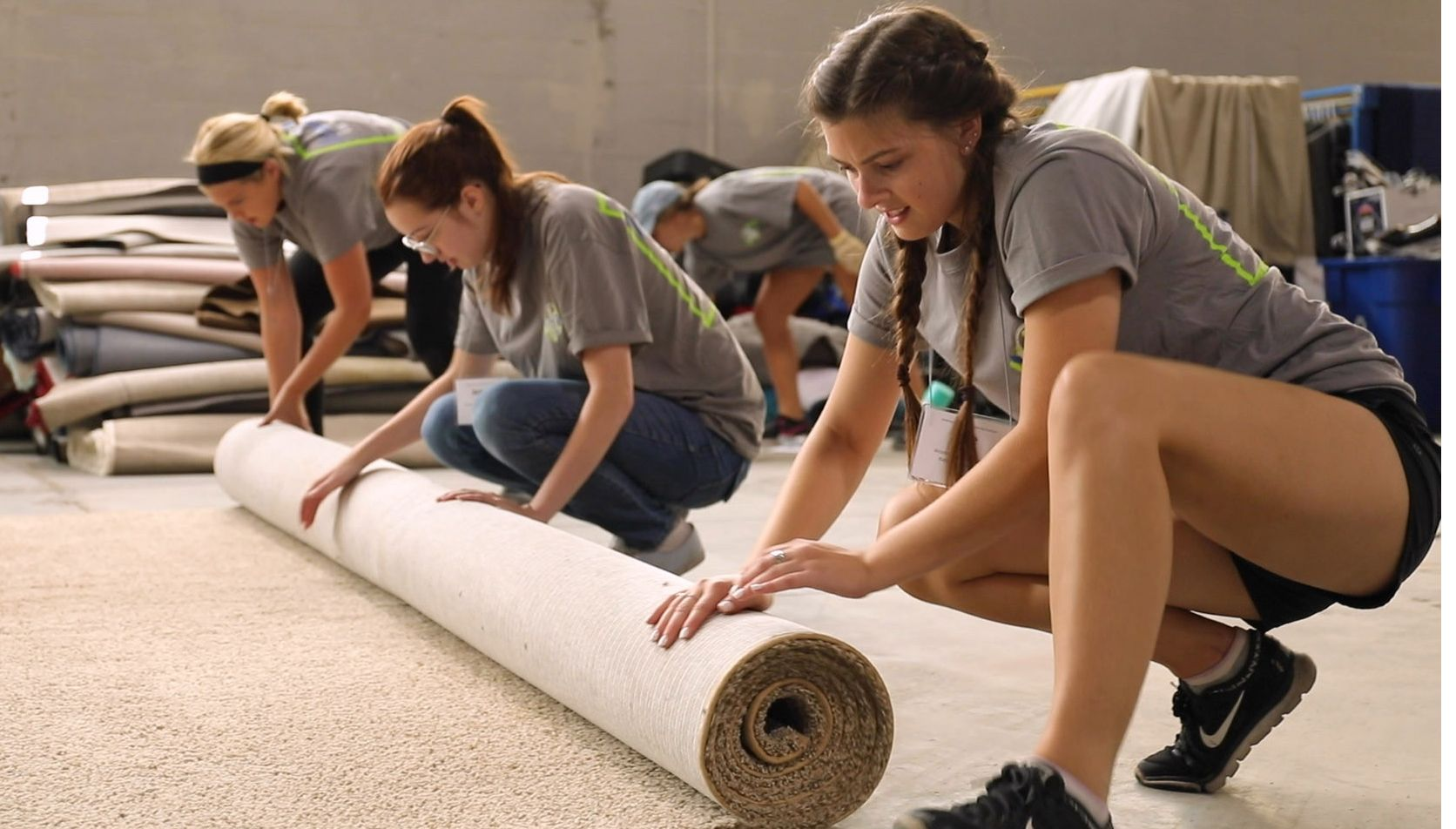 Three female students roll up a section of carpet.