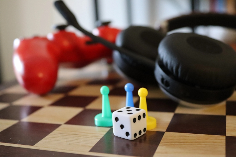 Dice, game pieces, a video game controller and headset grouped on a chessboard