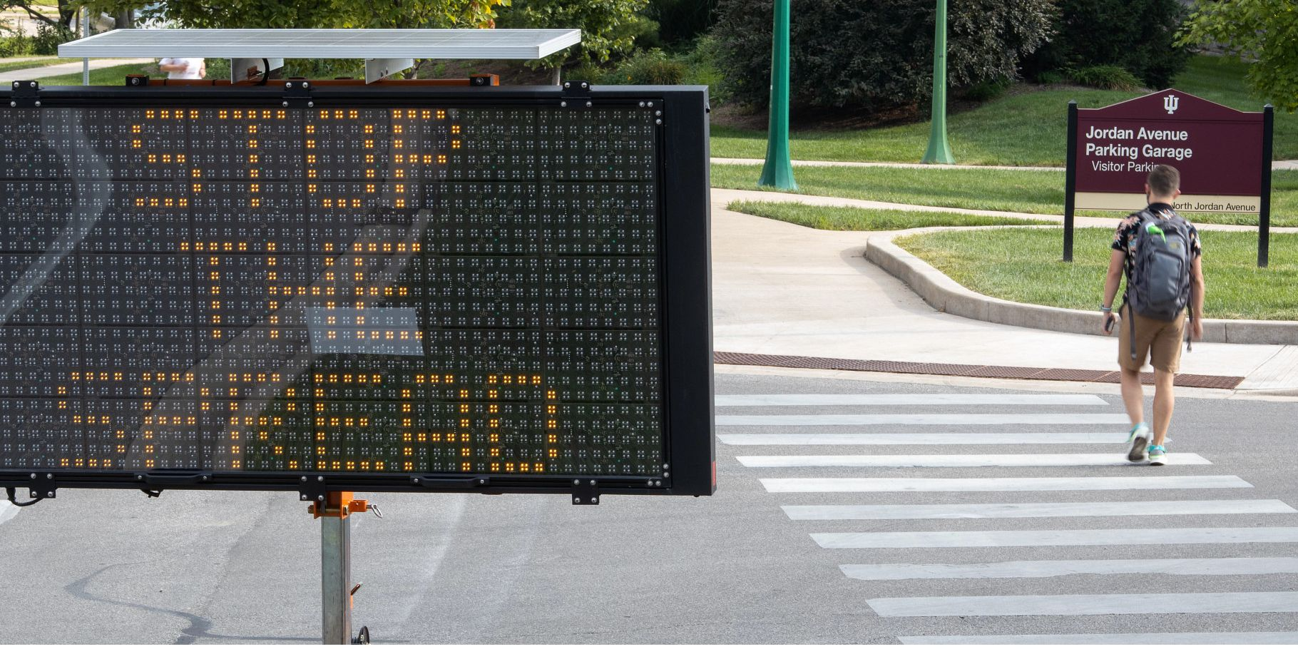 a student crosses the street past a digital sign that says stop the spread