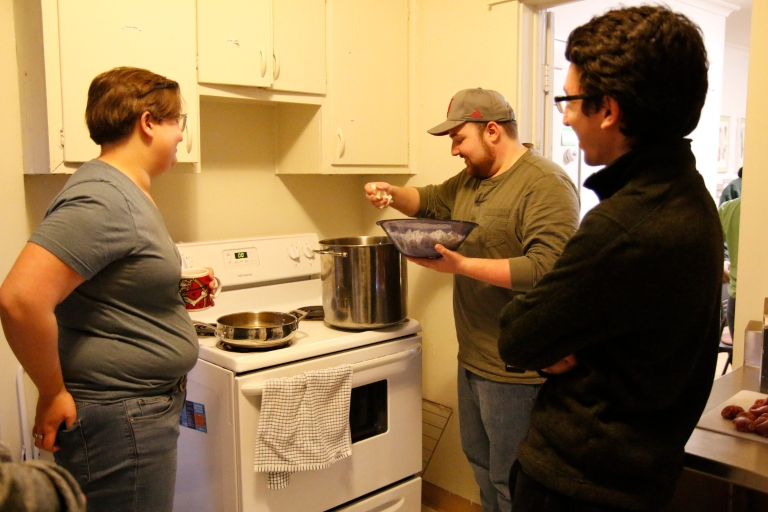 Three students stand around a stove in a kitchen