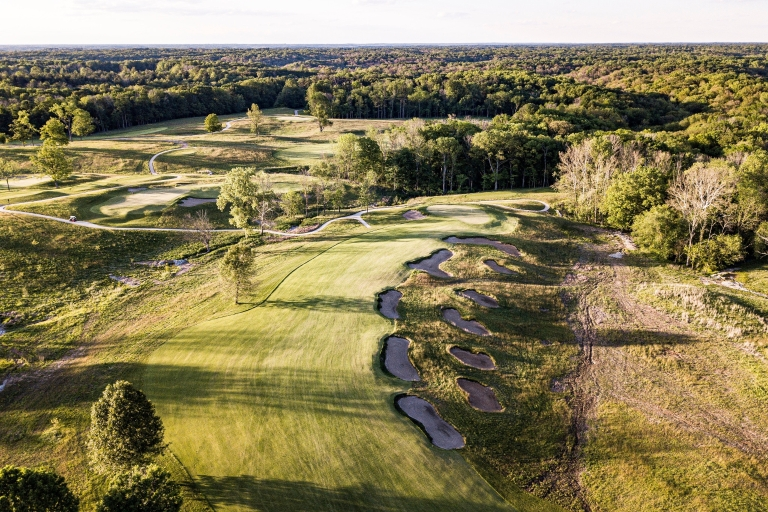 An overhead view of a golf course fairway with bunkers along the right side.