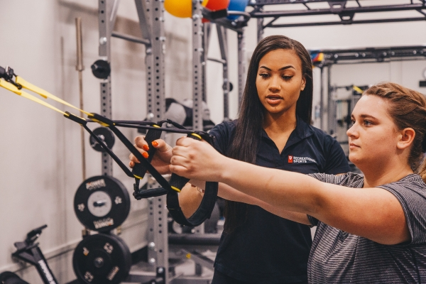 A member of Campus Recreation instructs an exercising student.