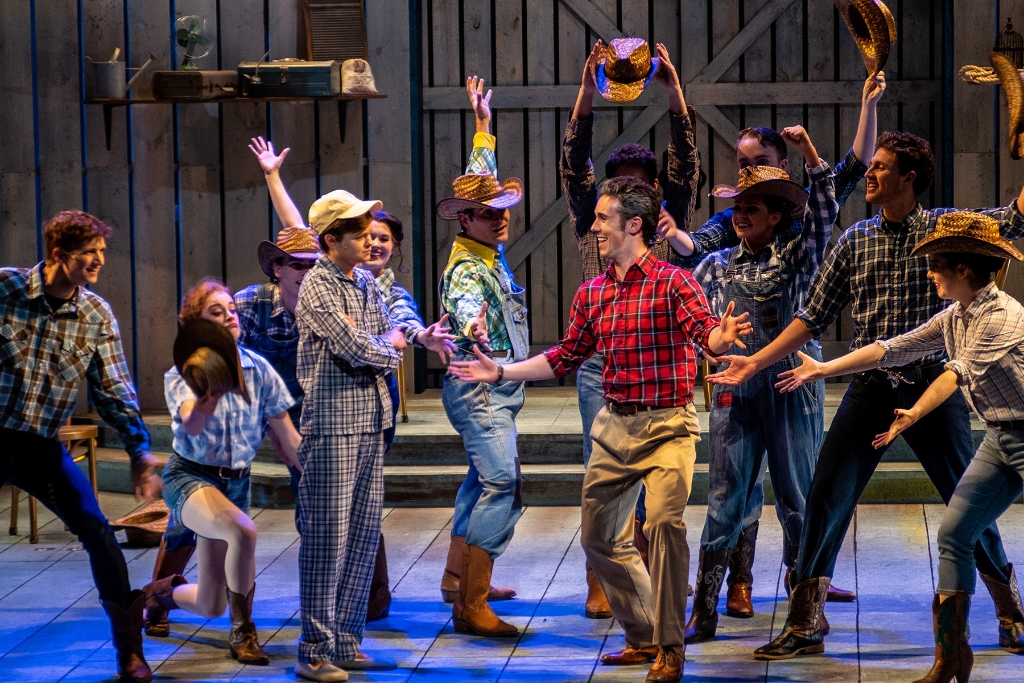 "Cast members in flannel shirts on stage for a production of ""Big Fish"""