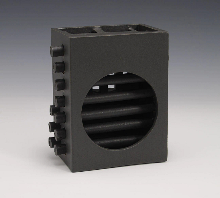 Artwork that is black glazed stonewear, a box with a circular window and rods.