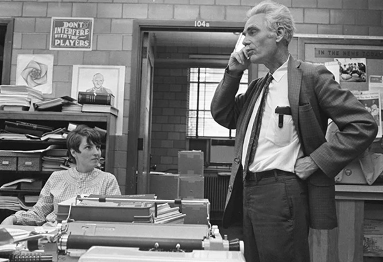 A black and white photo of a woman looking at a man standing up talking on the phone