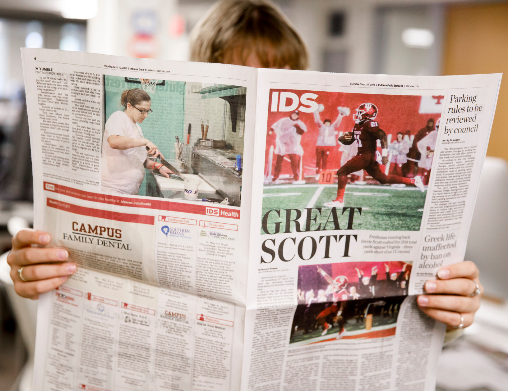 student reading a student newspaper