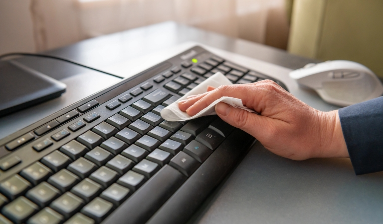 a hand cleaning a computer keyboard with a wipe