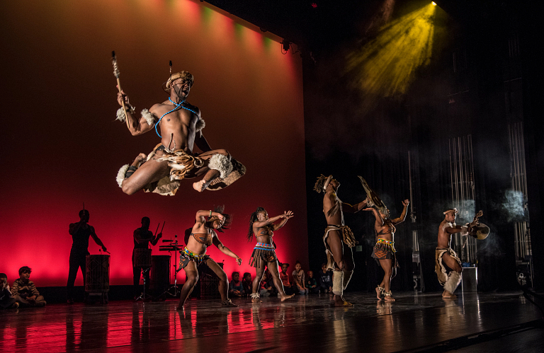 A man in costume jumps as Step Afrika performs