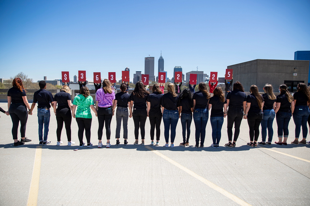 Students on top of sports garage hold signs  with Indianapolis skyline in the background.