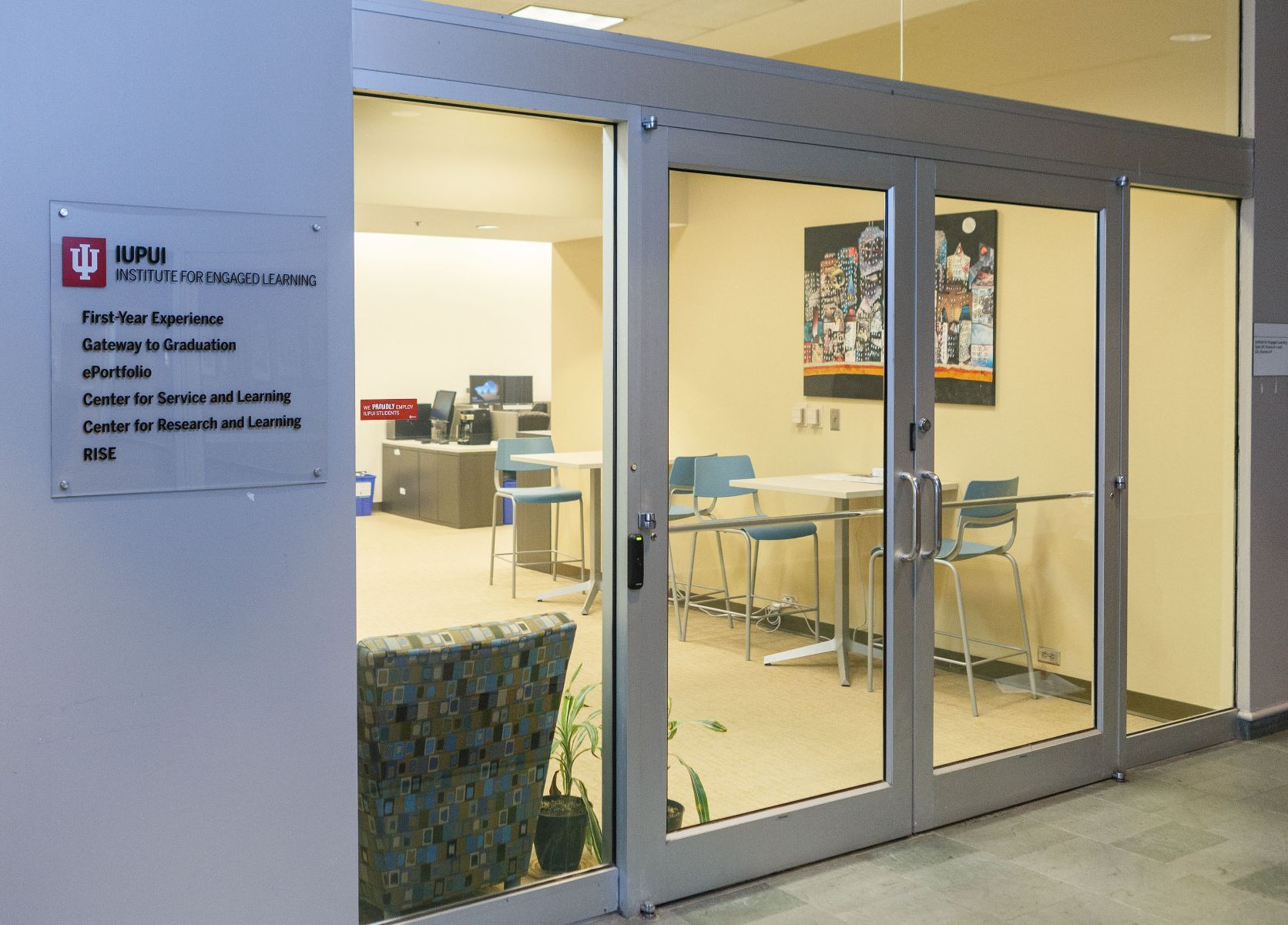 Photo of the front doors and sign next to the institute's space in Hine Hall.