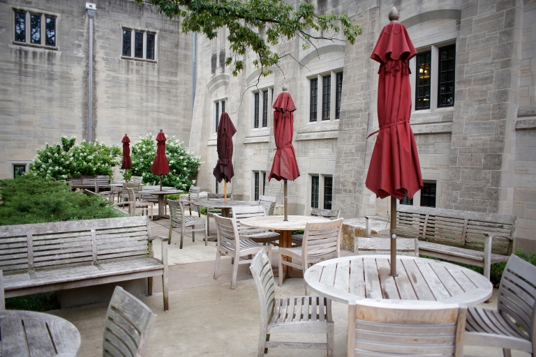 White tables with red umbrellas sit outdoor next to a limestone building.