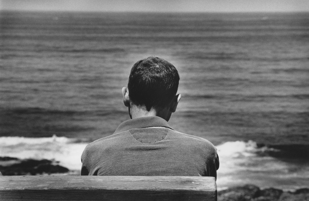 Man sits in front of ocean