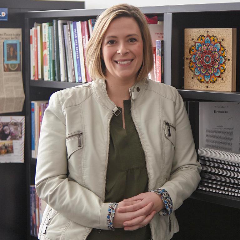 Eileen Misluk standing in front of a bookshelf.