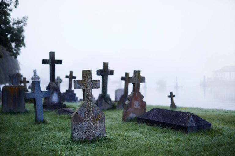 This photo is of a cemetery, with crosses on graves and fog rolling over the scene.