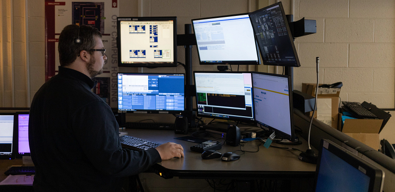 A man sitting in front of several computer screens