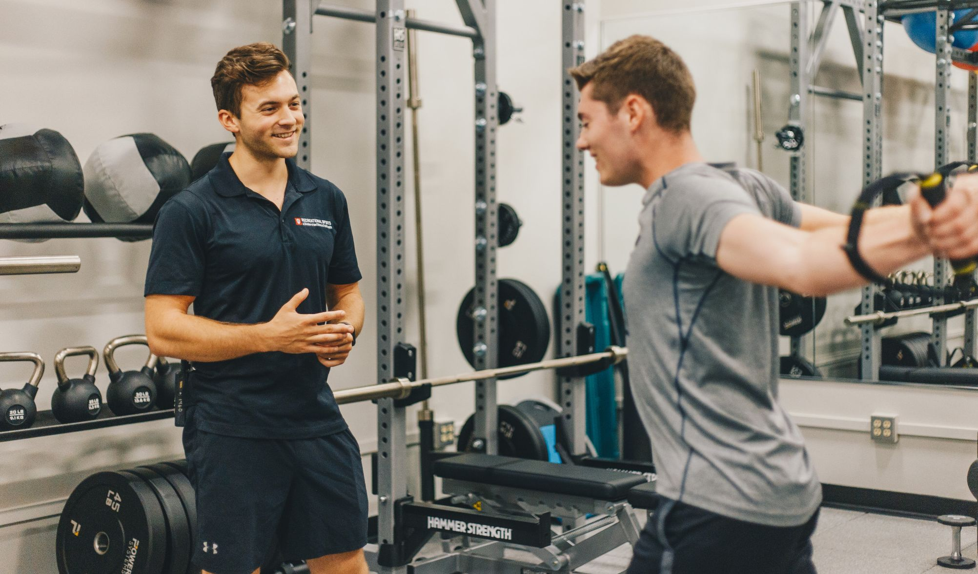 A personal trainer assists a client with a workout