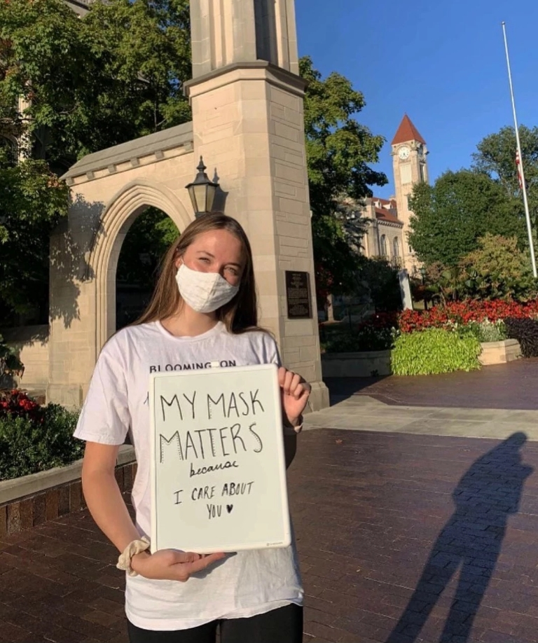 Arianna Smith holds a white board that reads my mask matters