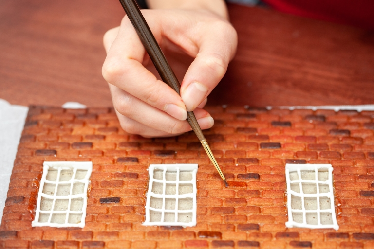 A hand paints pieces of a gingerbread house