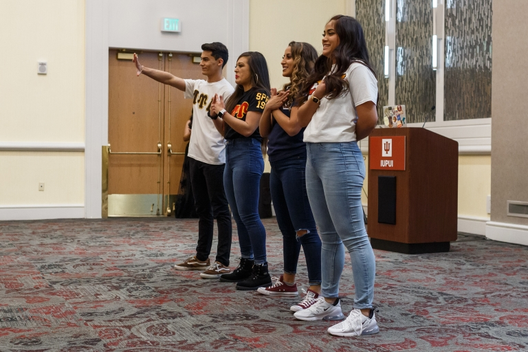 Members of the Multicultural Greek Council stand in a line showing their groups' hand signs.