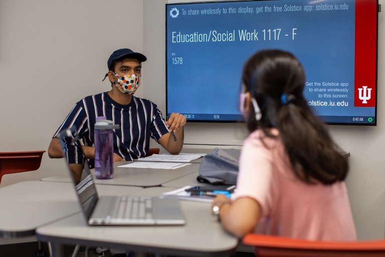 Two students in masks learn in a classroom