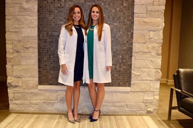 Two women stand next to each other in their white dentist coats
