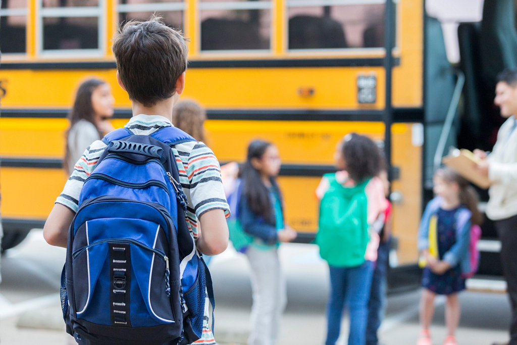 Elementary students wearing backpacks wait to board a school bus