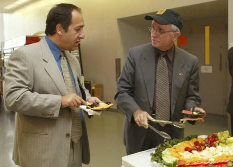 two men standing at a buffet food table grabbing food