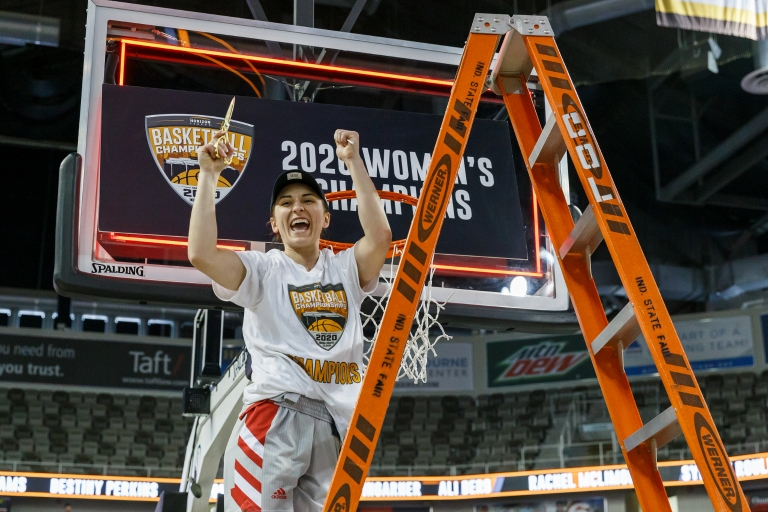 women's basketball player stands on a ladder celebrating cutting part of the net