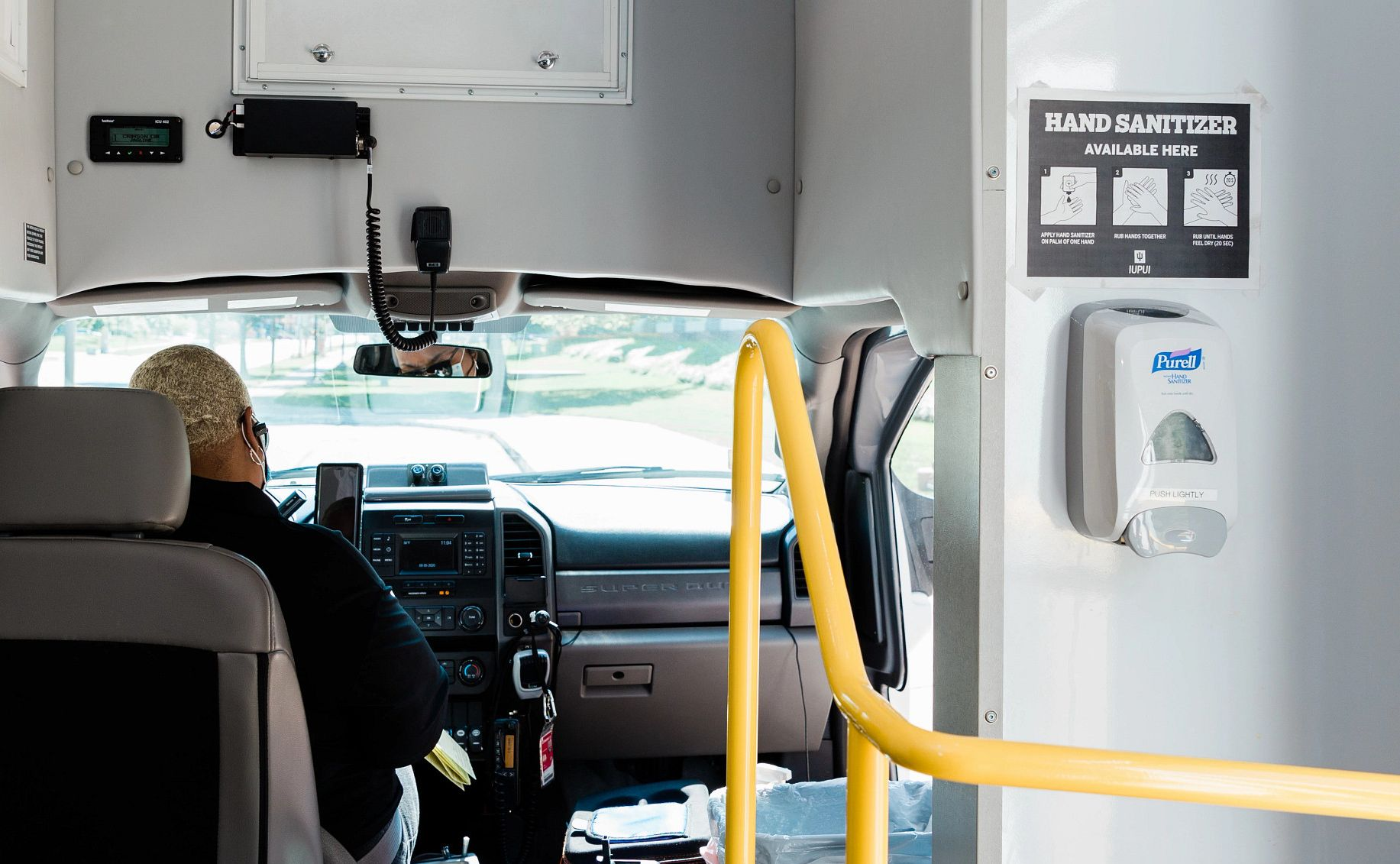 Interior of a bus with a hand sanitizer dispenser and a driver wearing a mask