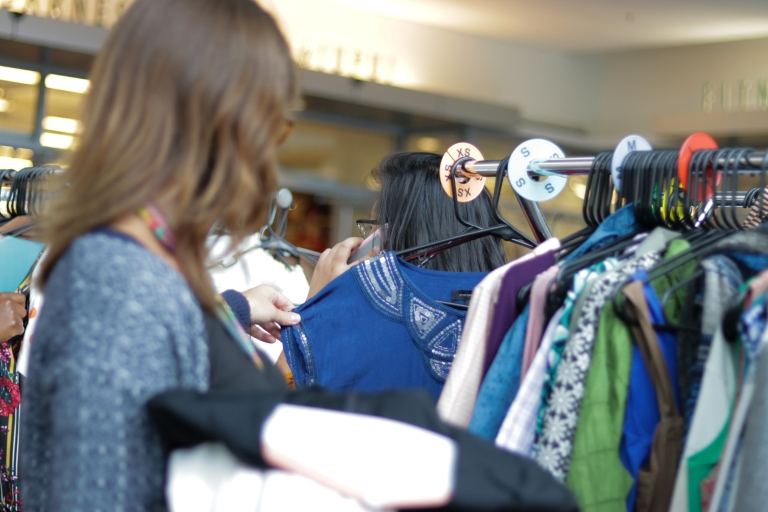 A student looks at a blue shirt during a Paws' Closet pop-up shop.