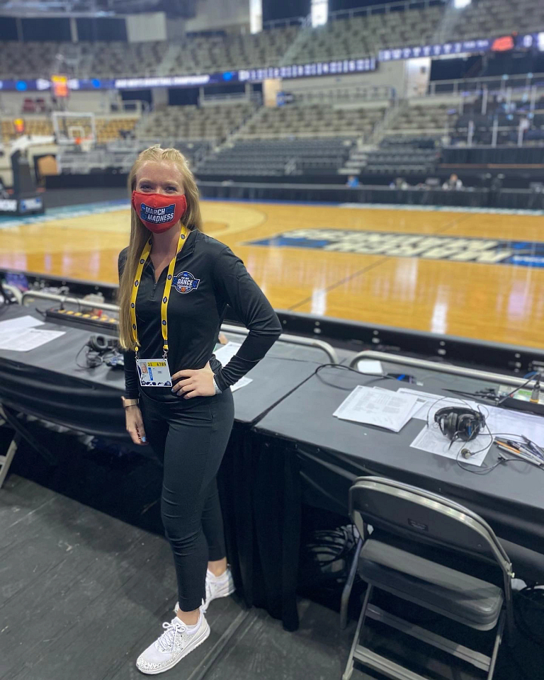 A woman wearing a March Madness mask stands by a table near the basketball court