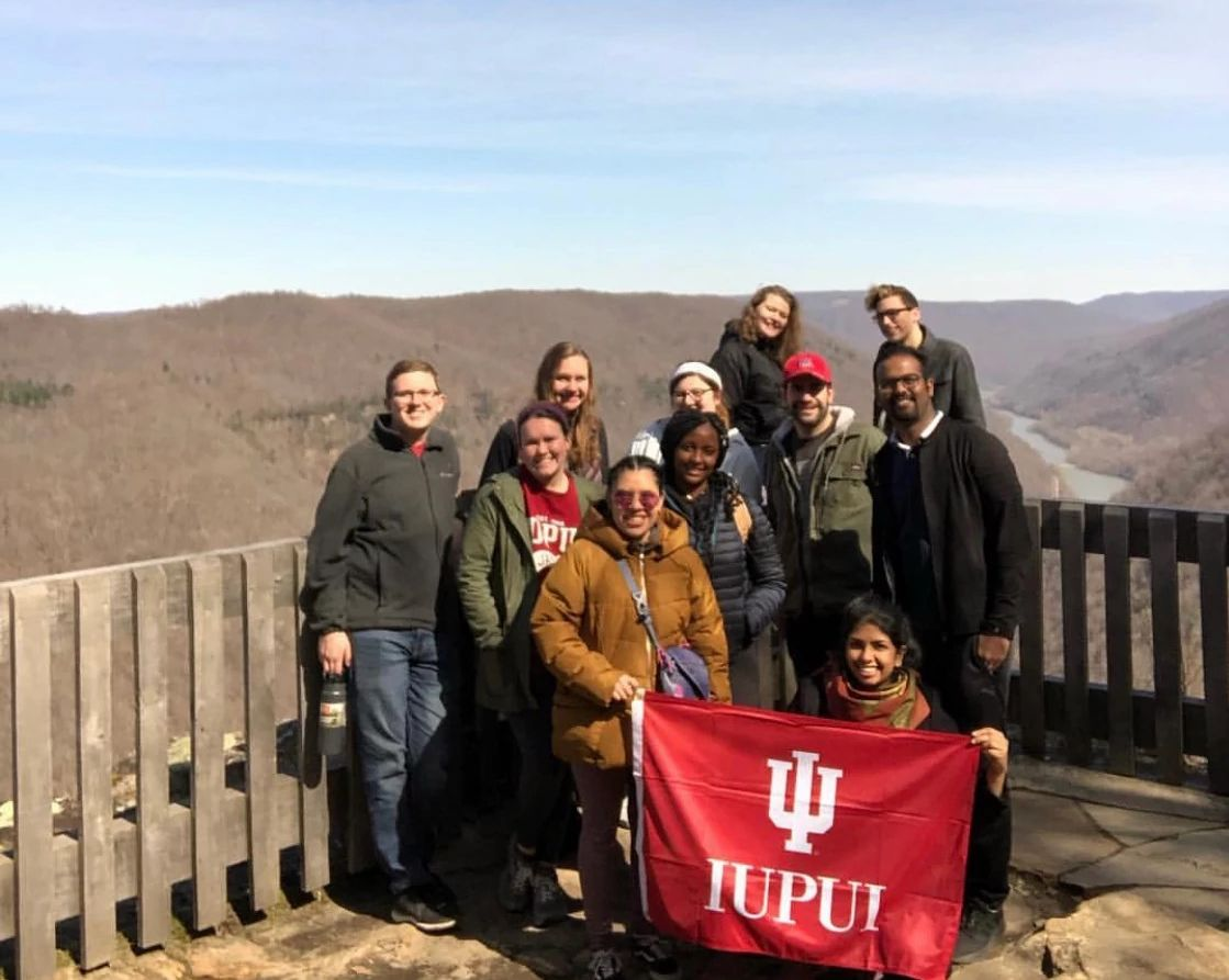 A group of IUPUI students pose with their flag overlooking a ravine.
