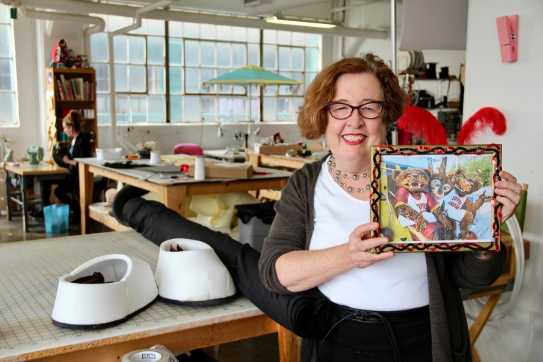 Jennifer Smith stands in her mascot-creating Indianapolis studio with a picture of Jawz and Jazzy