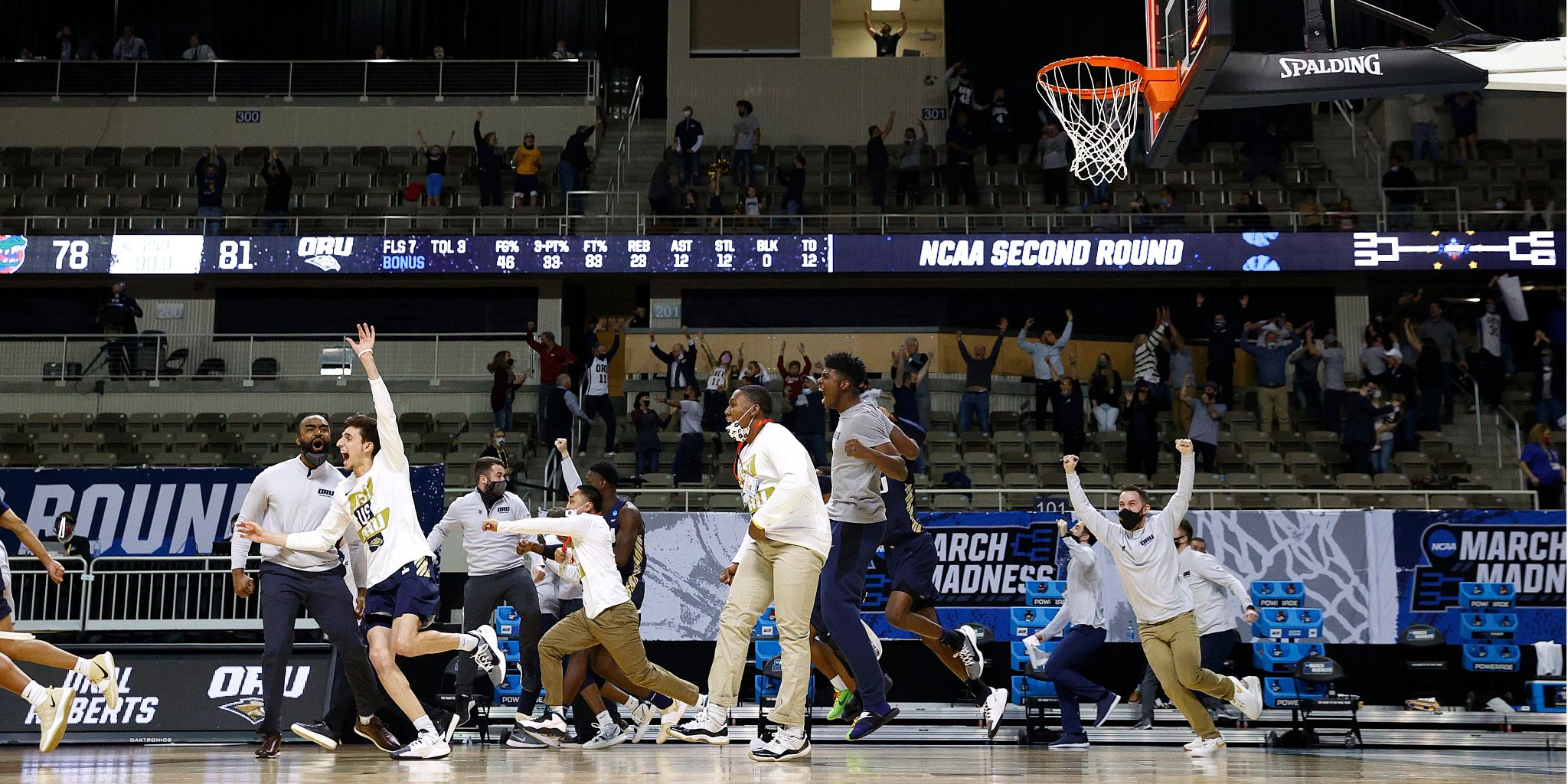 players and coaches jump off the bench in celebration