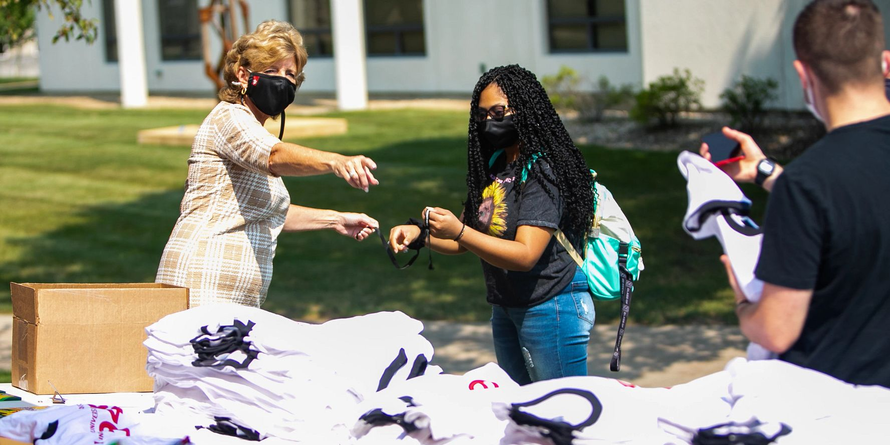 a masked woman points a masked student to a table of T-shirts