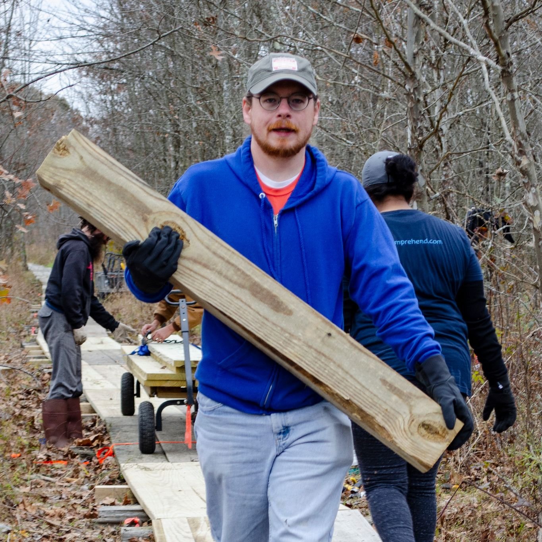 Daniel Pierce hauls a wooden post down the boardwalk.