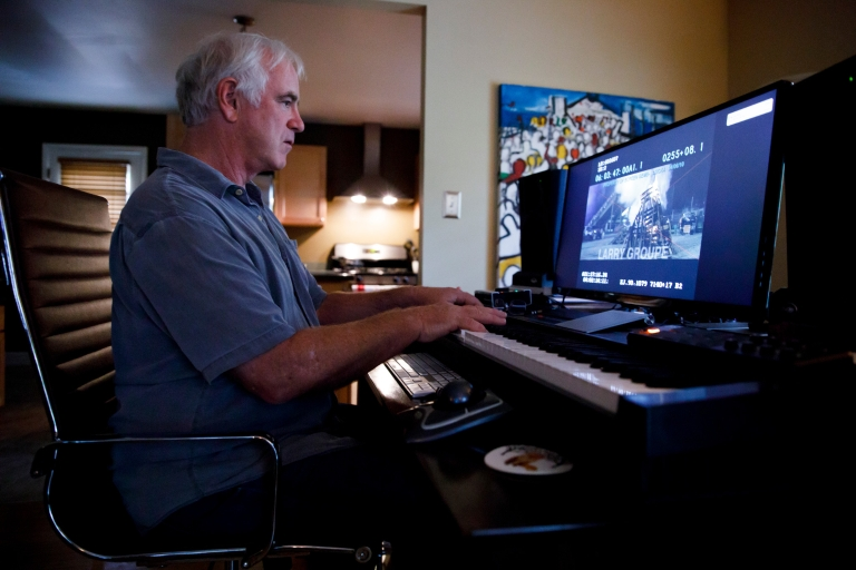 Larry Groupe works at his computer and keyboard on a movie score