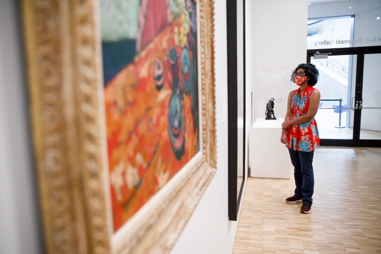 A woman wearing a mask looks at art in a museum
