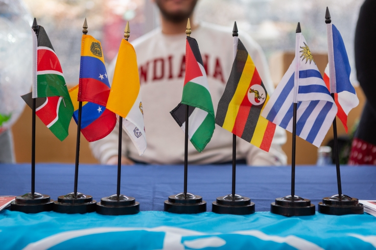 Flags from countries around the world are displayed on a table with an IU student in the background