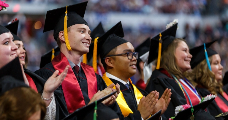 IUPUI students in caps and gowns clapping during a ceremony