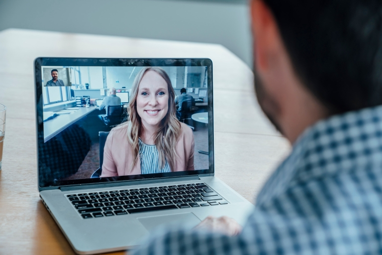 A woman and a man talk virtually using videoconference software